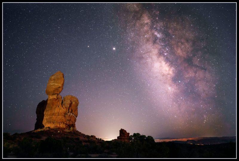 Oblong rock on top of rock pillar, faint triangle of light, cloudy Milky Way, 2 bright dots.