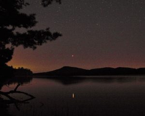 A ridgeline in the background, a lake in the foreground, and Mars reflecting in the lake.