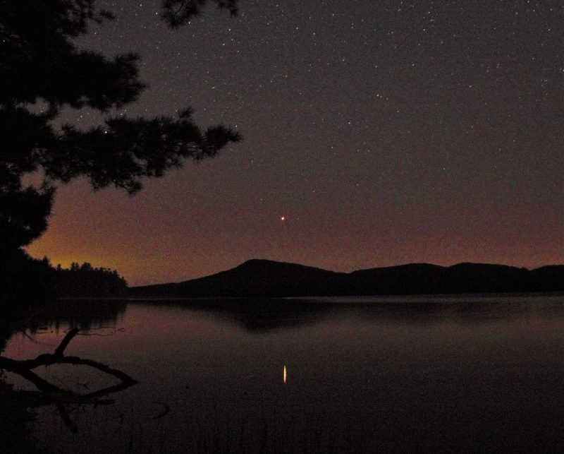 A ridgeline in the background, a lake in the foreground, and red Mars reflecting in the lake.