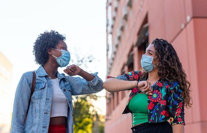 Two people wearing masks, bumping elbows.