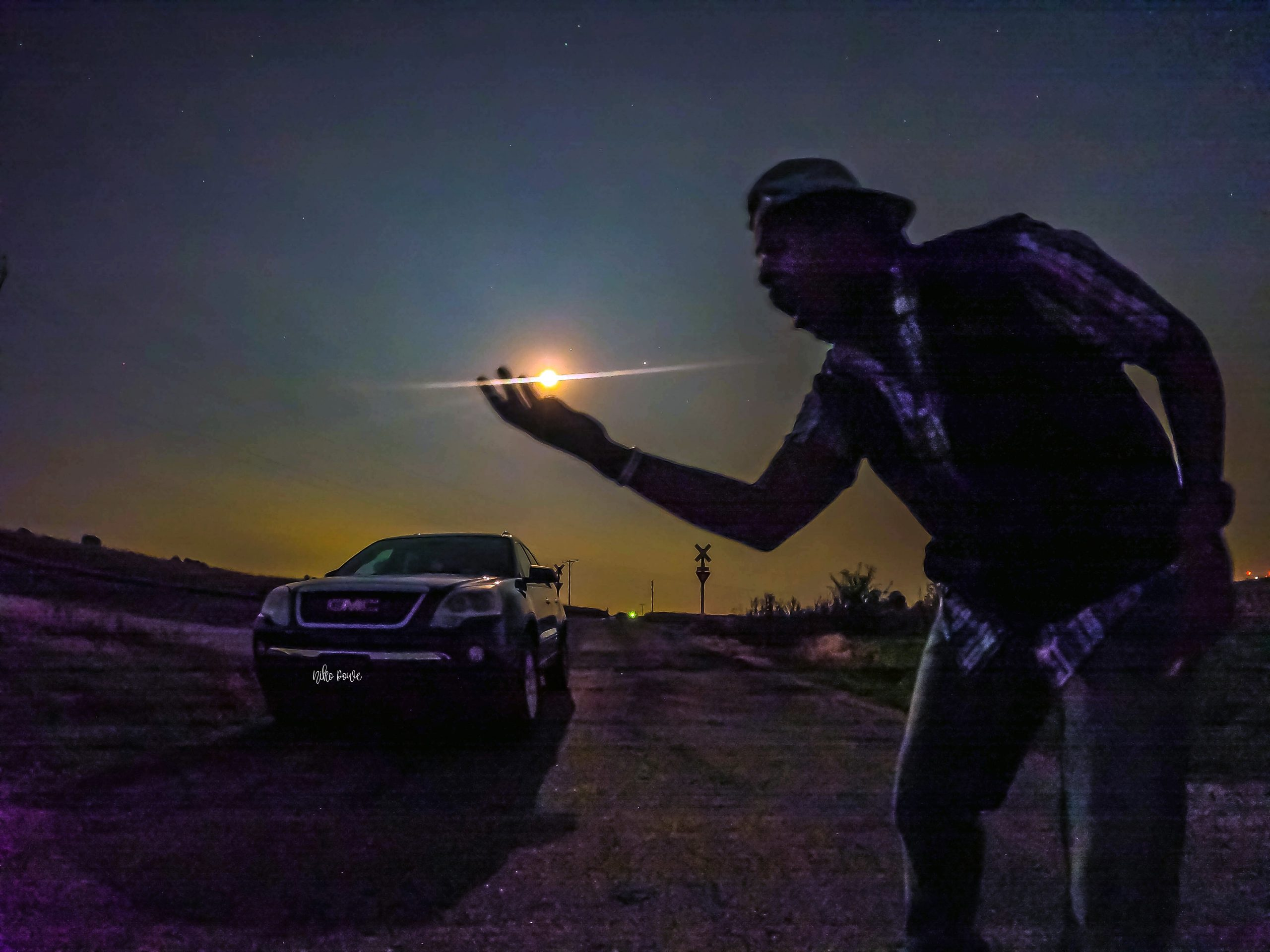 A man on a country road at night, holding out his hand as if holding the moon and planets.