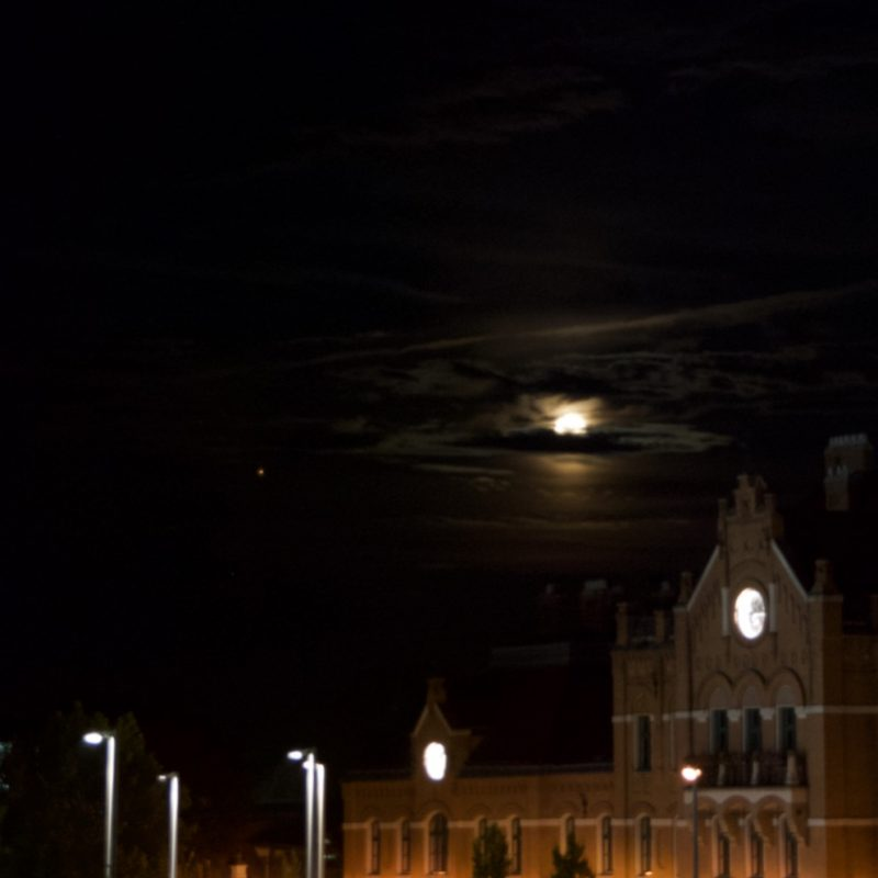 Moon and Mars peeking through clouds above an old European style building, perhaps a church.