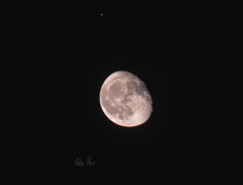 Telescopic image of the waning gibbous moon and very tiny dot of Mars.