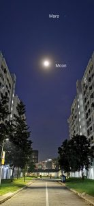 The moon and Mars above buildings in Singapore.