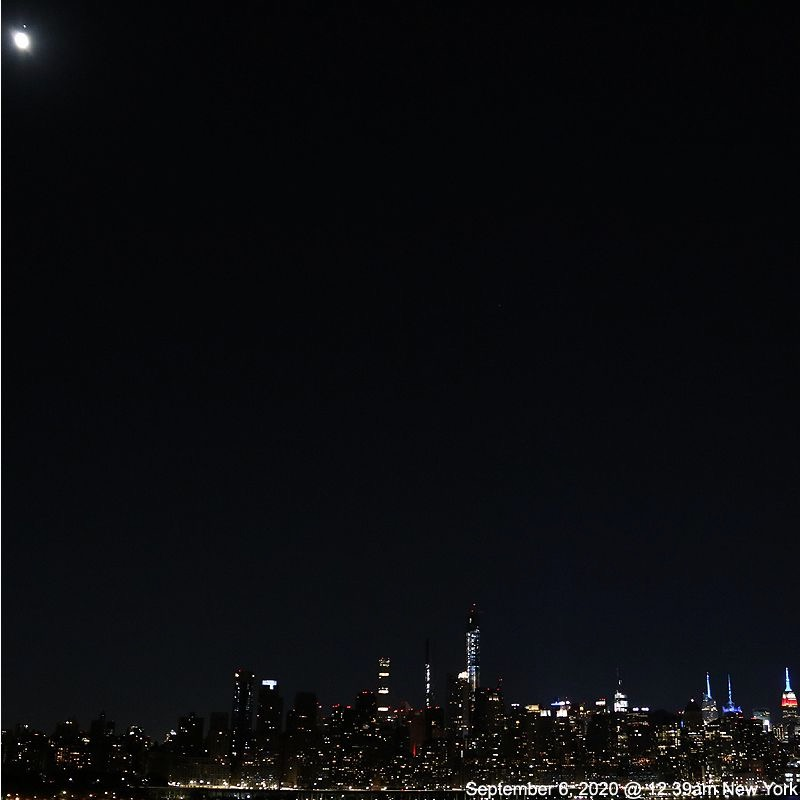 Moon and tiny dot of Mars over glittering New York City nighttime skyline.