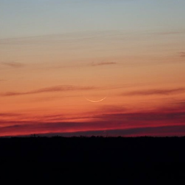 A barely visible crescent moon set against bright red-orange twilight.