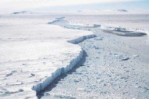 An iceberg calving from a glacier.