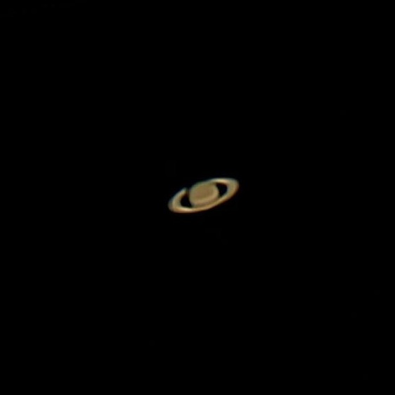 Brownish telescopic photo of Saturn, showing the rings.