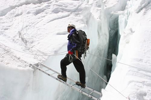 A man standing on a narrow ladder across a deep crevasse.