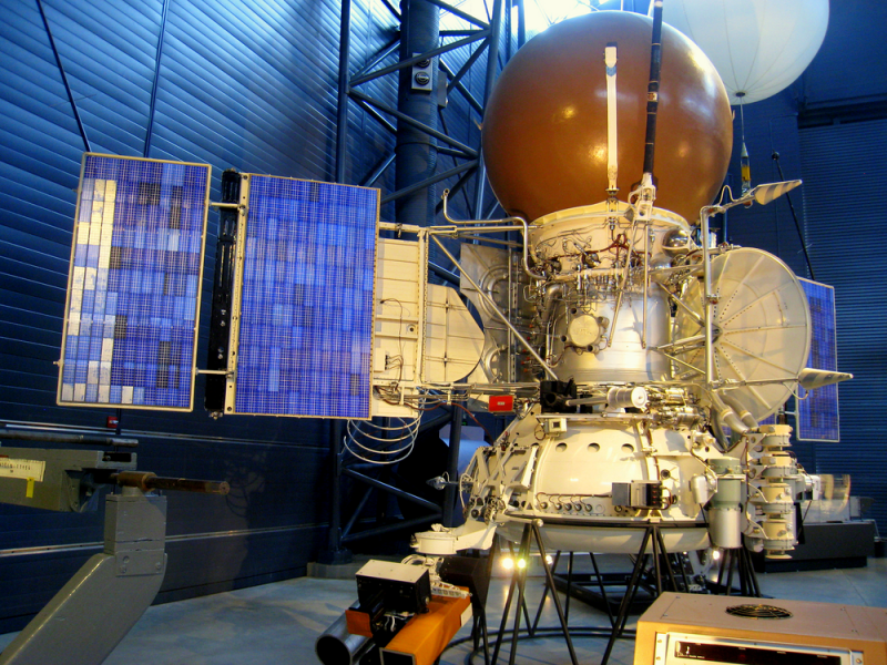 Spacecraft with cylindrical body, large, brown sphere at top, and solar panel wings.