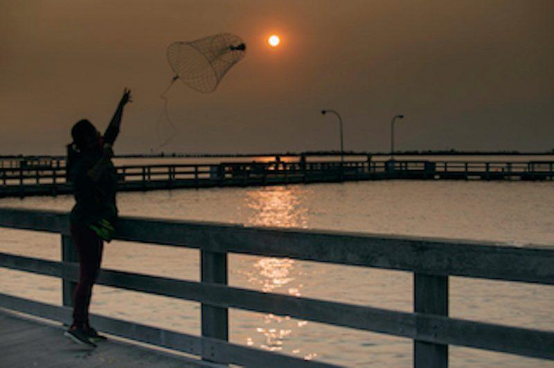 A woman standing on an ocean pier, throwing a net toward a reddish sun in a red sky.