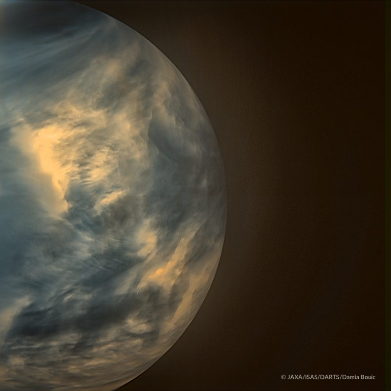 Part of a planet with dim yellow and blue clouds.