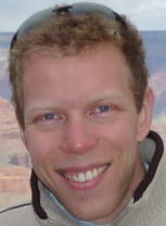 Smiling blue-eyed man with countryside in background.
