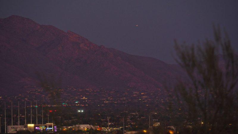 Dark mountain with bright reddish dot high in dark sky above.