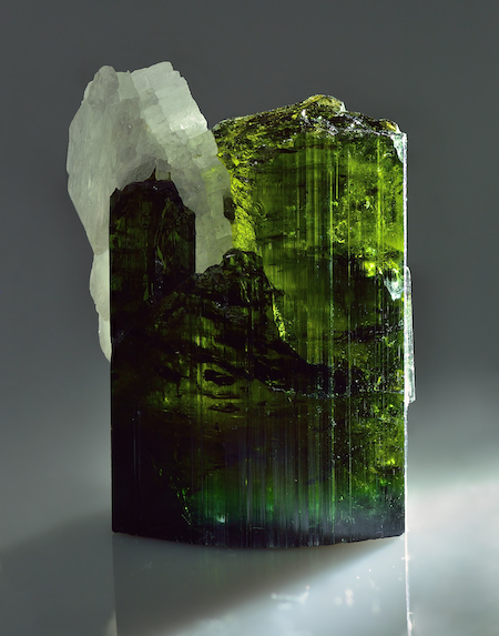 A squarish green translucent crystal. It also has some white crystals, albite, growing out of the top left of the main green crystal.