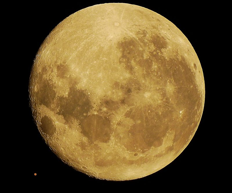 Nearly full yellow moon with red dot close to its lower left.