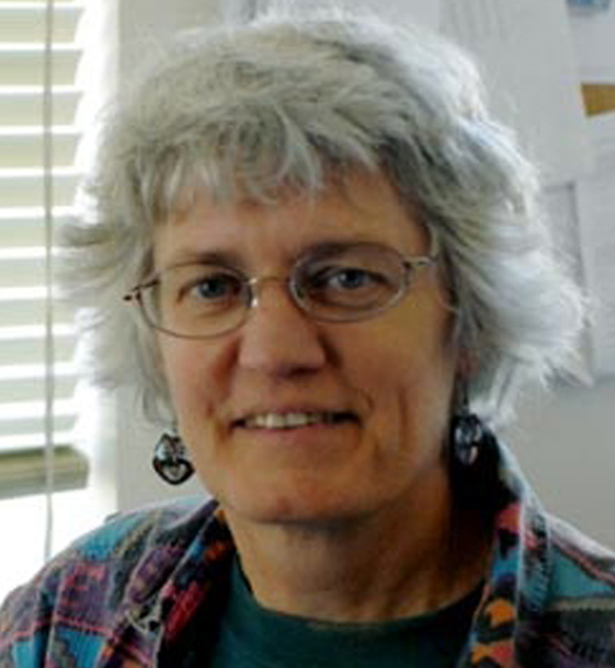 Smiling gray-haired woman with eyeglasses, with window blinds behind her.