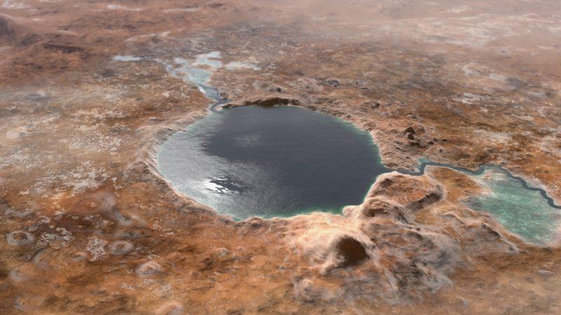 Circular lake with small river in brownish-reddish terrain.