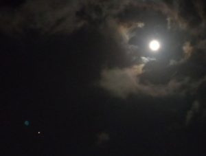 Glowing white moon in circle of partly-lit couds, with reddish dot to lower left.