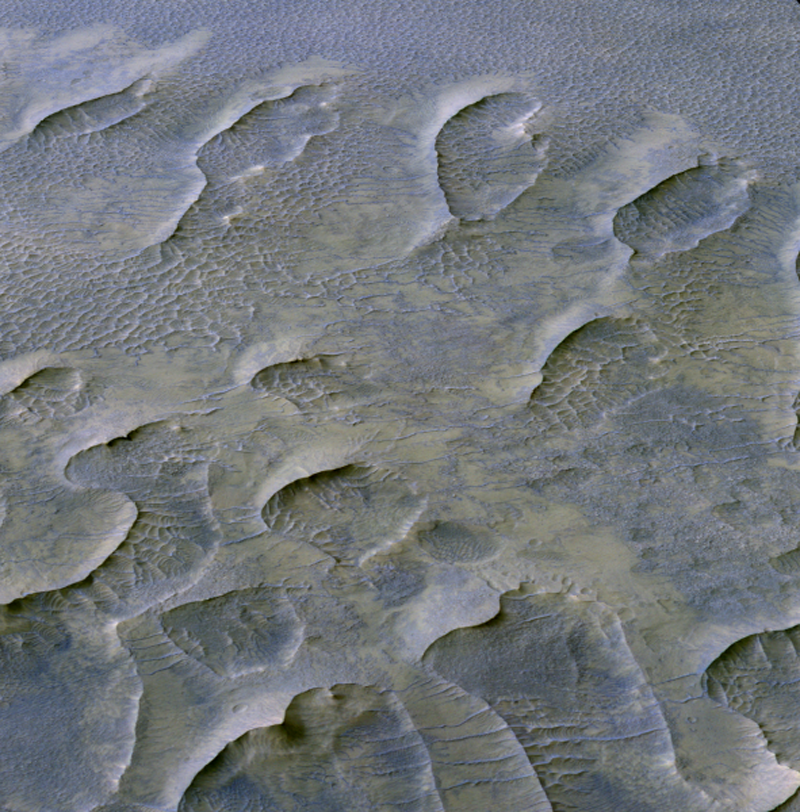 Orbital view of many crescent-shaped features on mostly smooth bluish background.