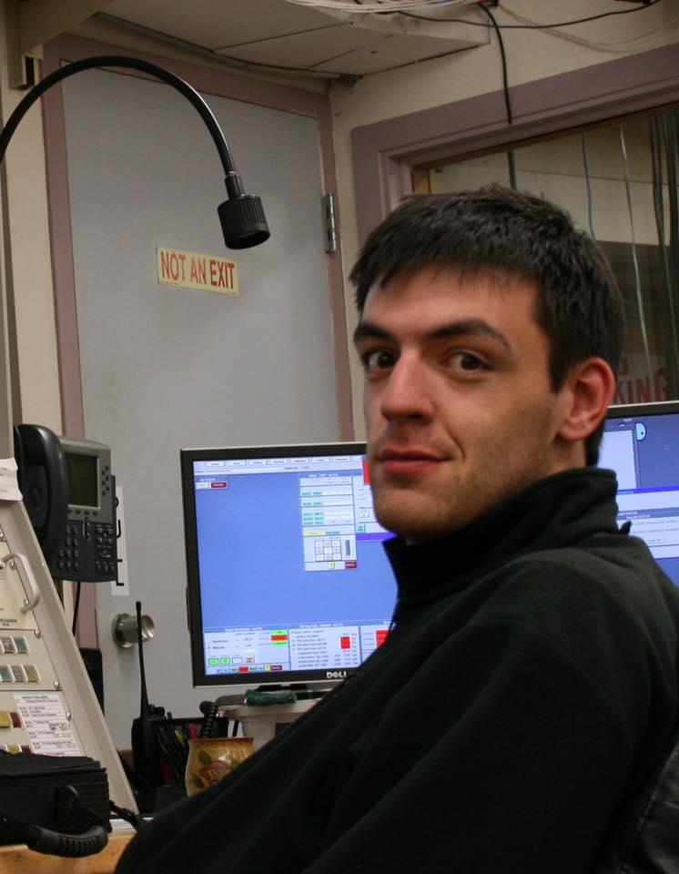Dark-haired man in turtleneck sweater with computer behind him.