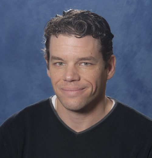 Smiling man with dark, curly hair.