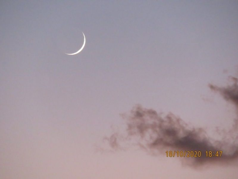 Thin white crescent moon in darkening blue sky with a few clouds.