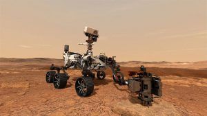 Robotic rover with long arm extended, on reddish rocky terrain with dusty sky.