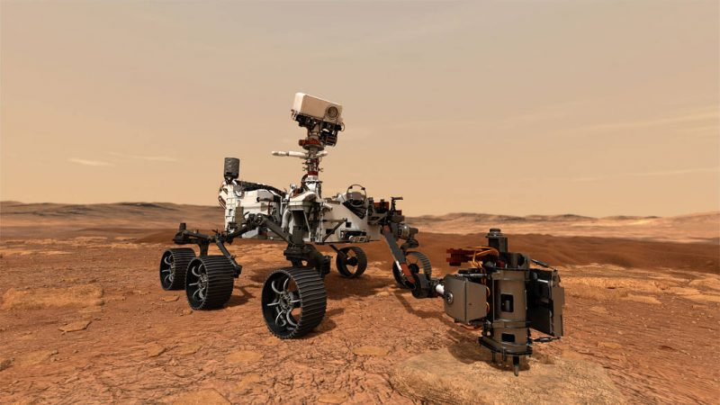 6-wheeled robotic rover with long arm extended, on reddish rocky terrain with dusty sky.