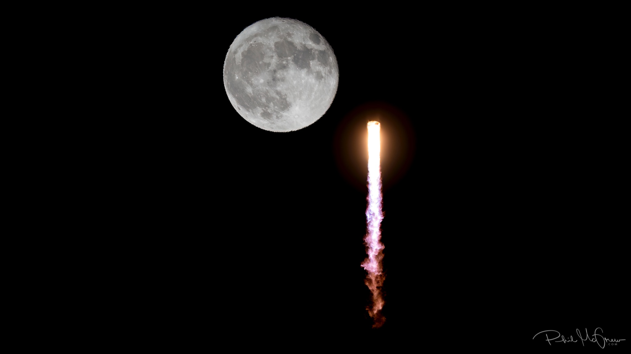 Nearly full moon with bright vertical streak of rocket exhaust near it.
