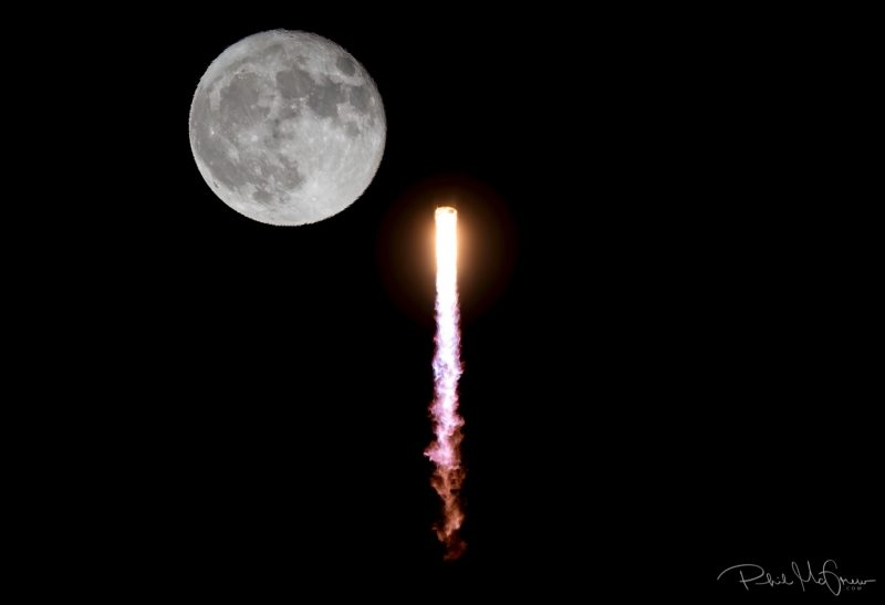 Nearly full moon and long brilliantly glowing vertical plume of rocket exhaust.