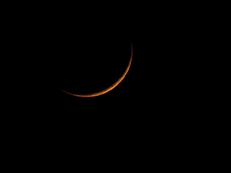 Thin orange crescent on black background.