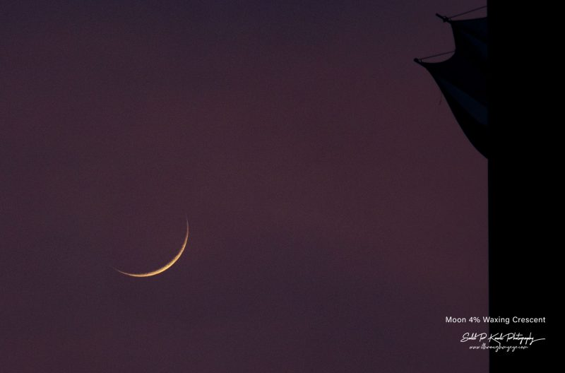Thin crescent moon in mauve sky beside tower.