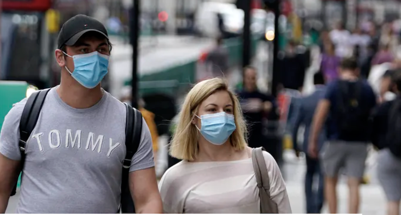 A man and woman walking on a city street, both wearing blue masks.