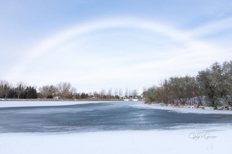 White rainbow above an icy river with trees on each side.