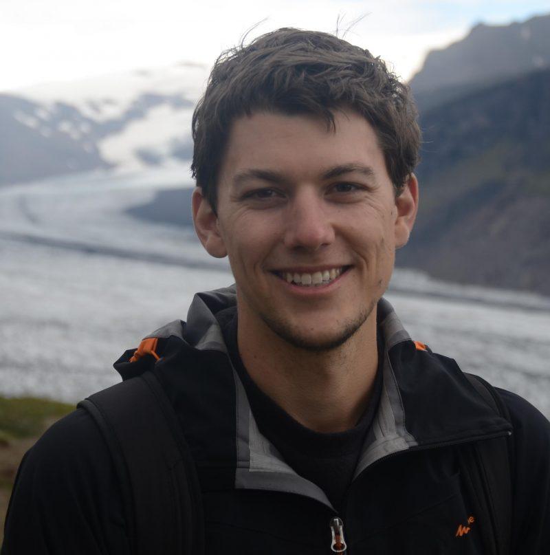 Smiling man with glacier behind him.