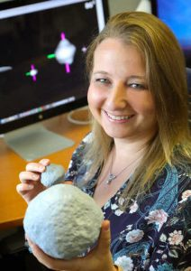 Image of Tracy Becker, a planetary scientist at SWRI, holding a 3D printed model of Psyche asteroid