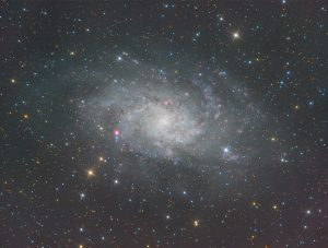 """An image of the Triangulum Galaxy, an almost """"face-on"""" galaxy, appears as a diffuse spiral formation. Blue, orange and red foreground stars are peppered across the field."""