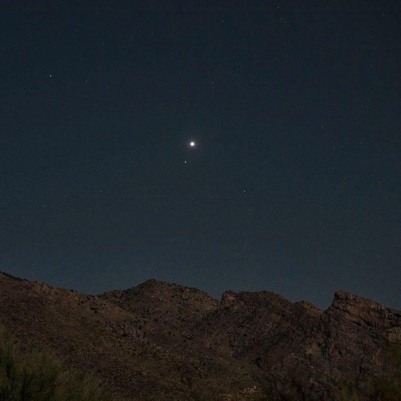 Bright planet Venus and fainter star Regulus, ascending over a ridgeline.
