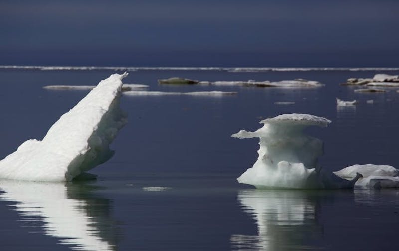 Large chunks of white ice floating widely separated in dark blue water.