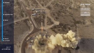 The New Shepard rocket is seen lifting off from its pad in the West Texas desert.