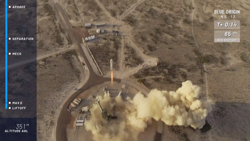 Aerial view of rocket lifting off on a pillar of flame with dust billowing around launch pad.