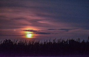 Mars and the Harvest Moon in a somewhat cloudy sky.