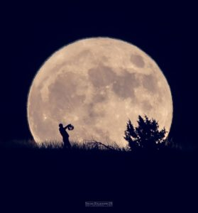 A giant full moon on the horizon, and a man walking in front of it, in silhouette, holding a jack'o'lantern.