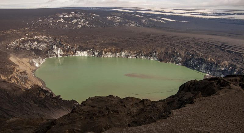 Crater filled with green water in brown landscape.