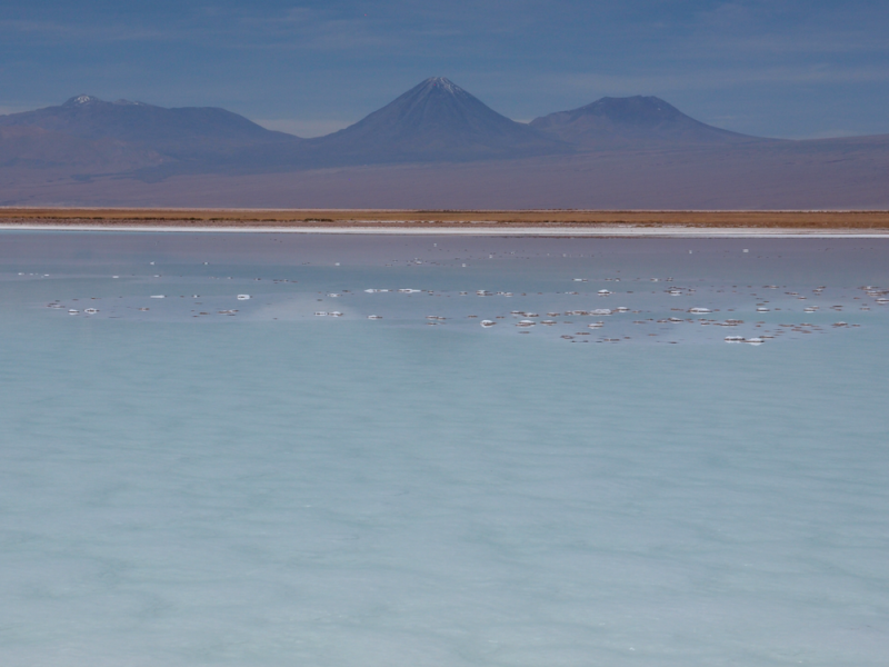 Very shallow water with barren coast and mountains in background.