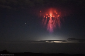 Red blob in night sky with long lightning-like tendrils hanging downward.