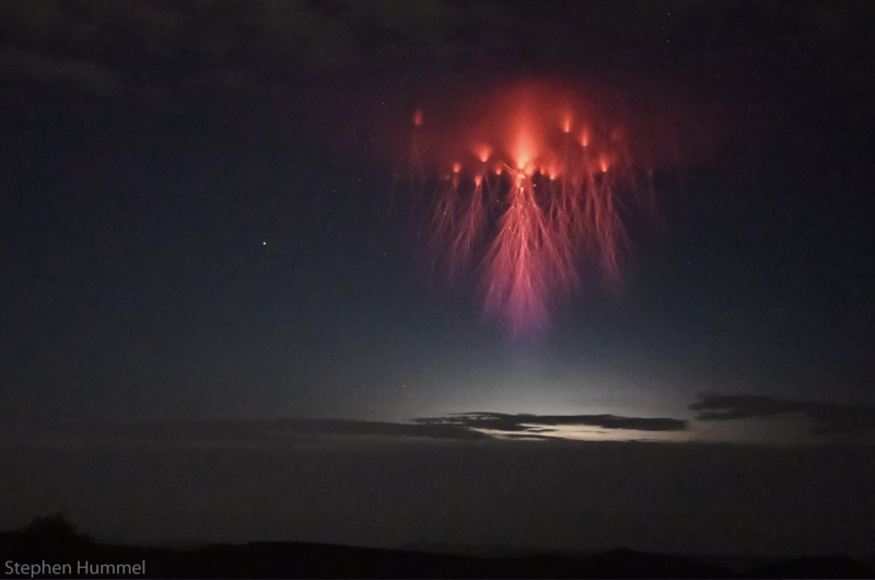 Red blob in night sky with many long lightning-like tendrils hanging downward.