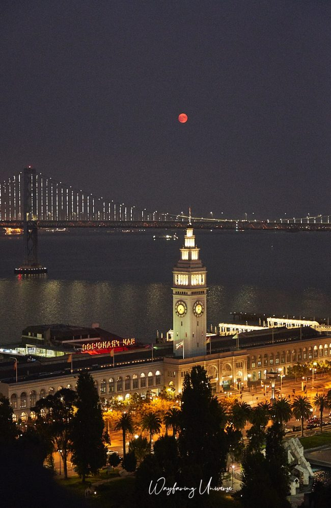 A very red, almost full moon shining over San Francisco.