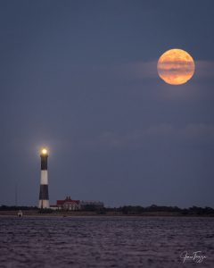 A golden full-looking moon, shining next to a lighthouse.